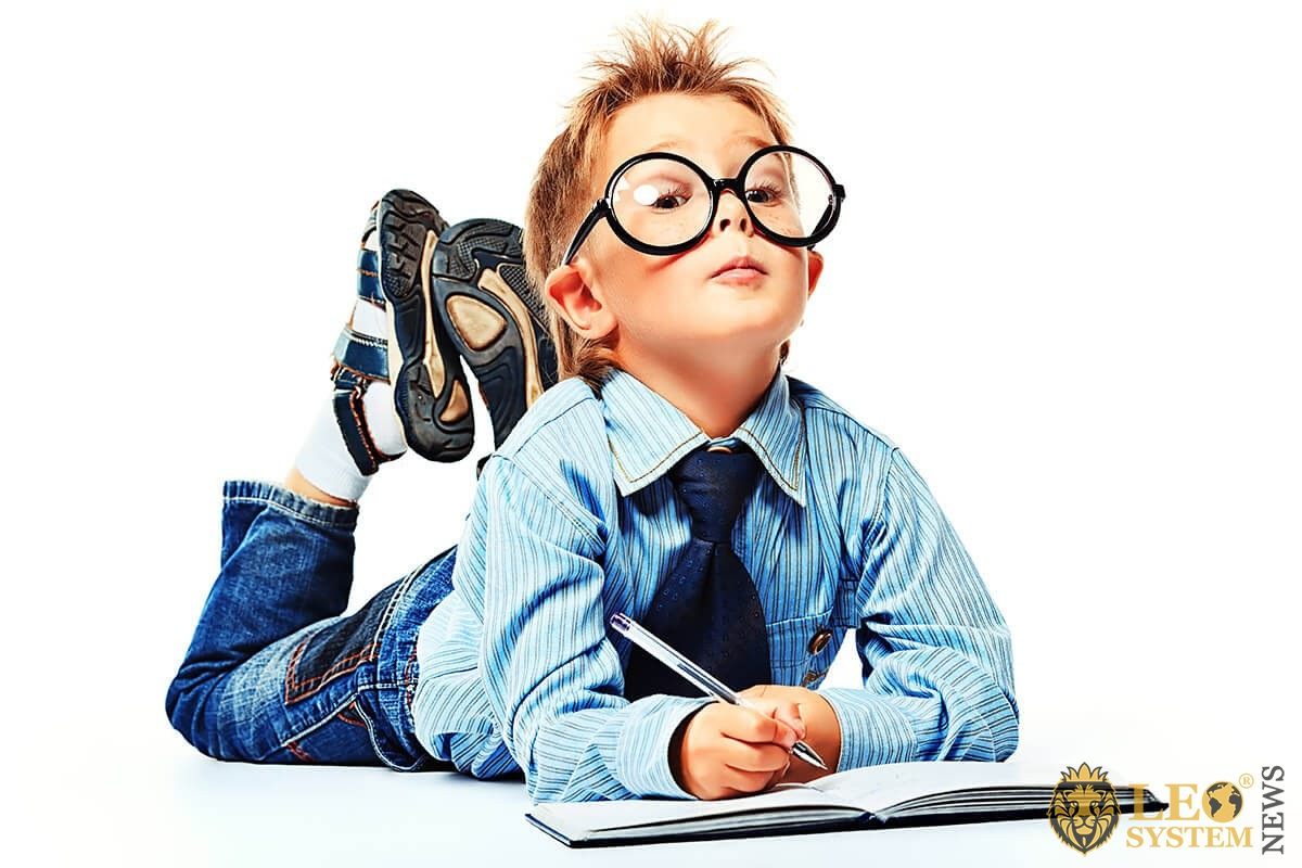 Smart child in glasses with a notebook and pen