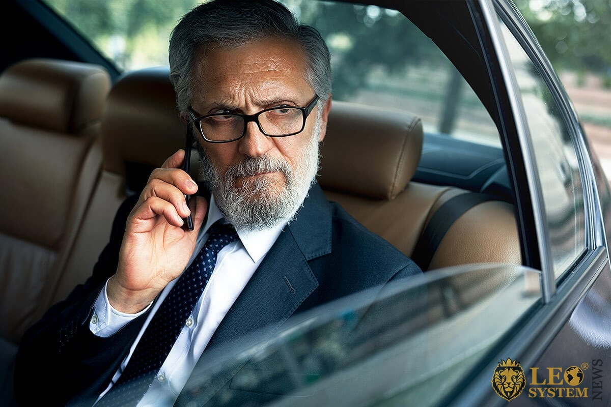Wealthy man sitting in the back seat of a car and talking on a cell phone