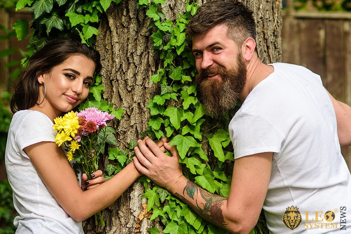 A man gives flowers to a woman by a tree
