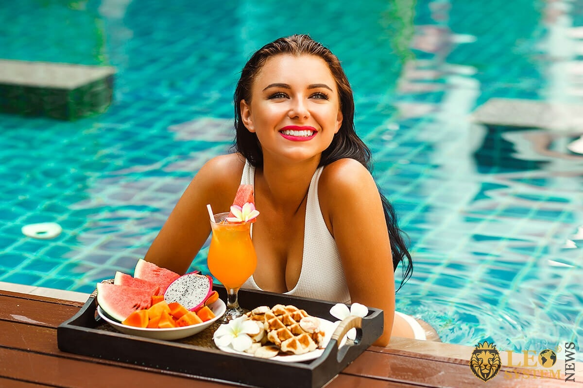 Charming woman having breakfast in the pool