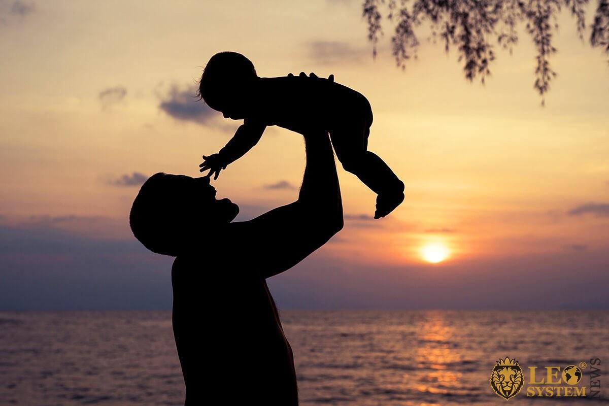 Father raises his child above his head