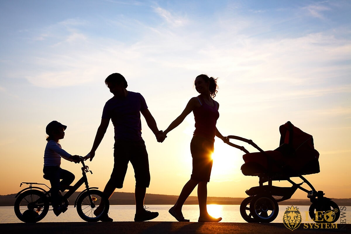 Family walk by the sea with a baby stroller and a second child on a bicycle