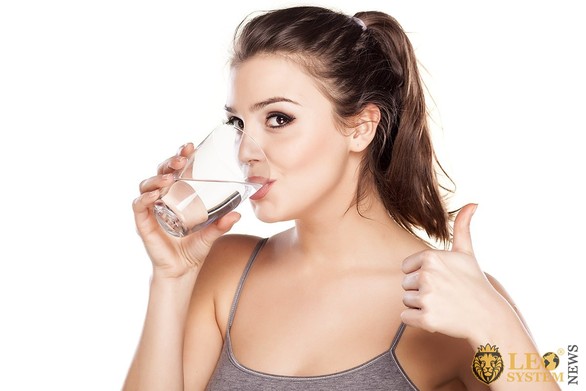 Woman drinks clean water from a glass