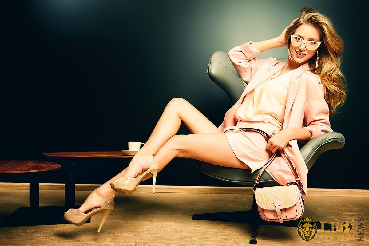Woman with beautiful long legs sits in a chair
