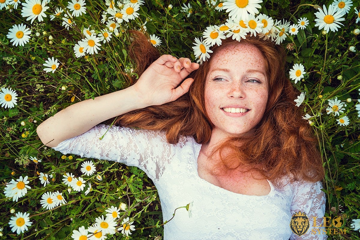 The girl lies in the flowers of daisies