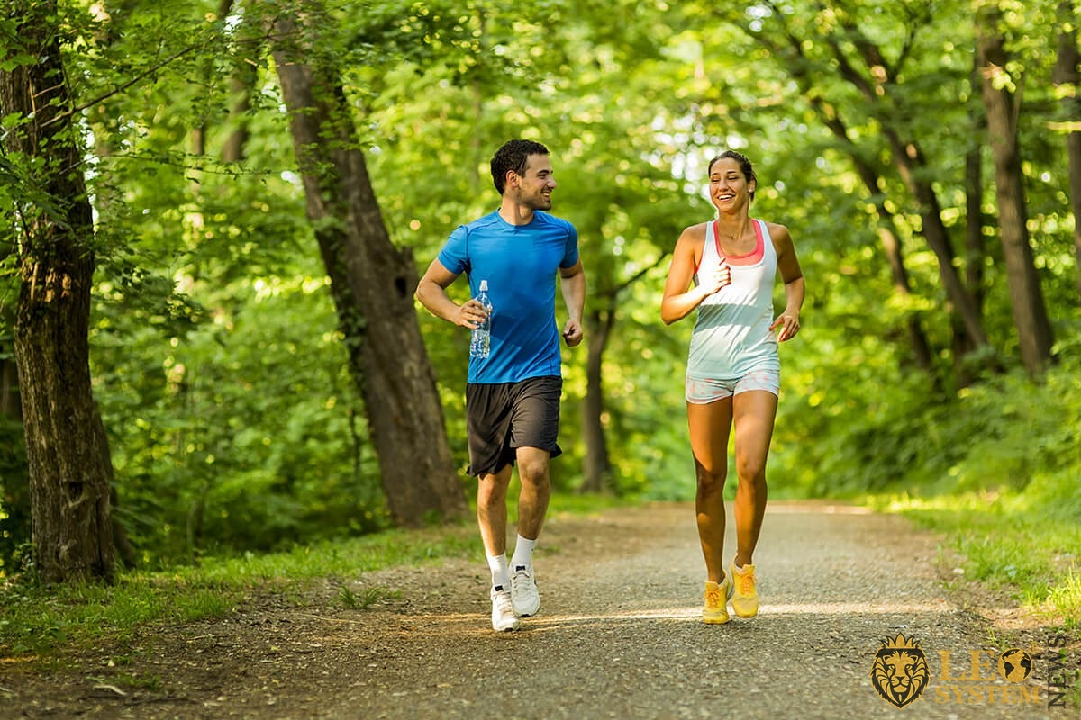Man and woman run through the forest