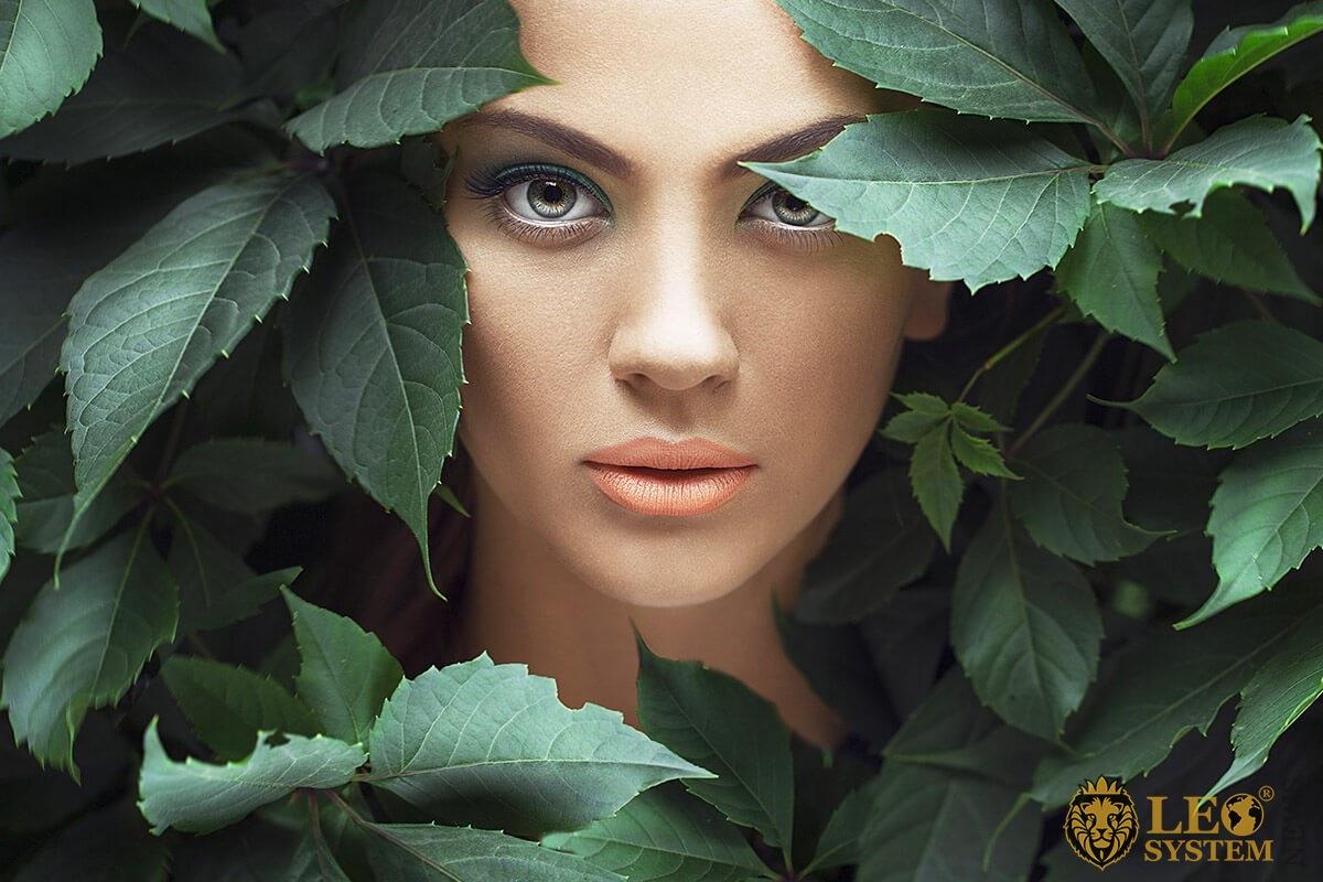 Female girl looks through the foliage