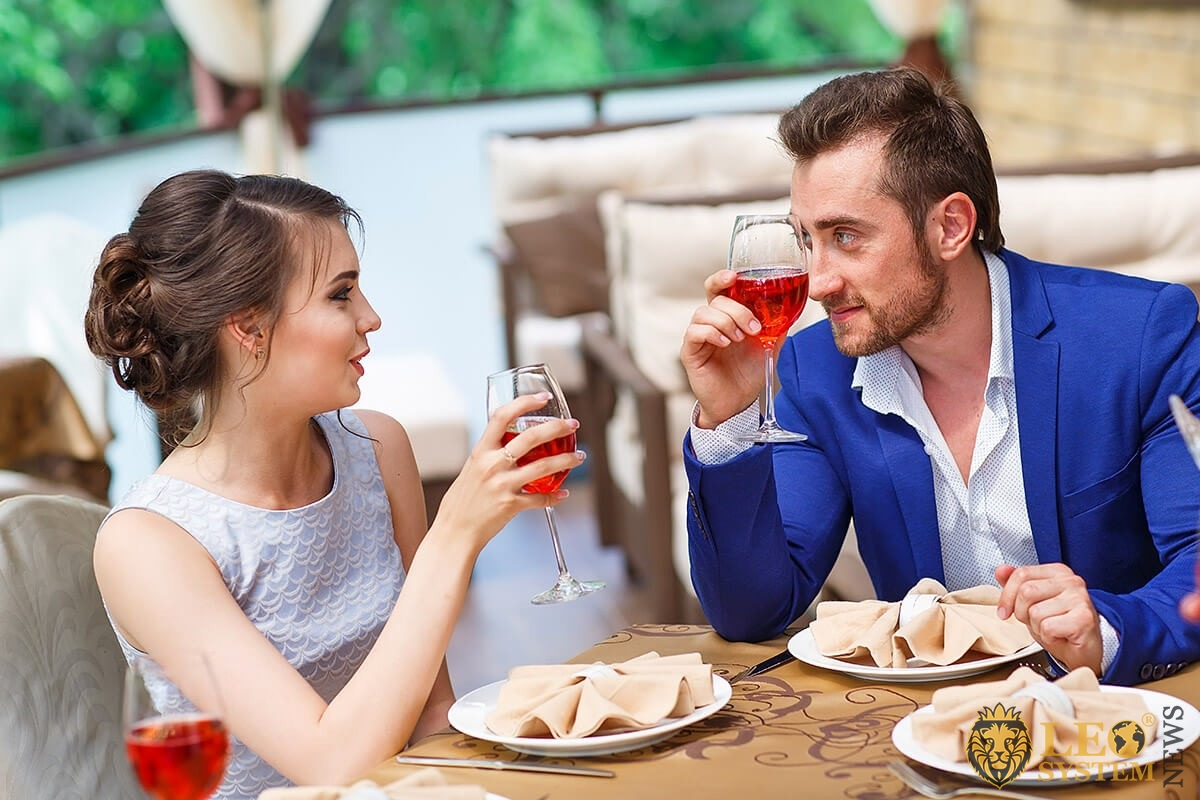 A man attracts a girl with his gaze and drinks wine