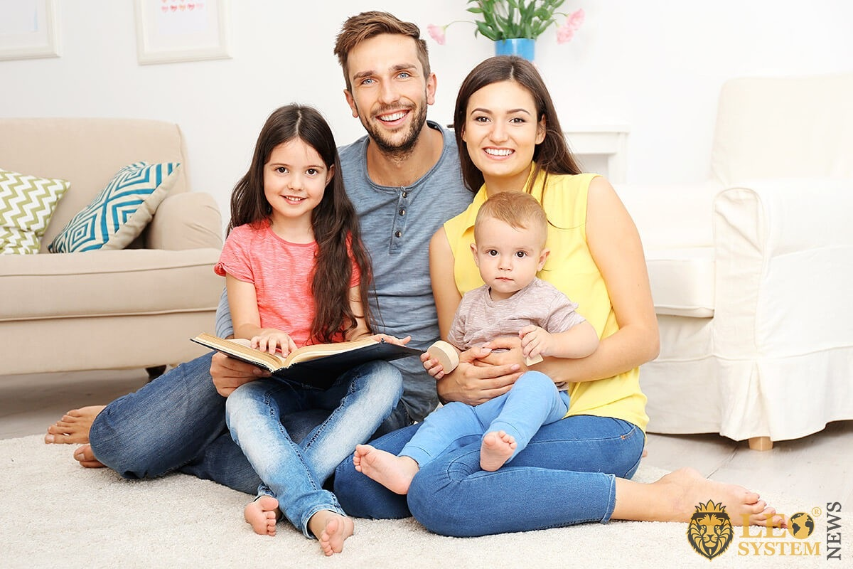Married couple with two children are reading a book