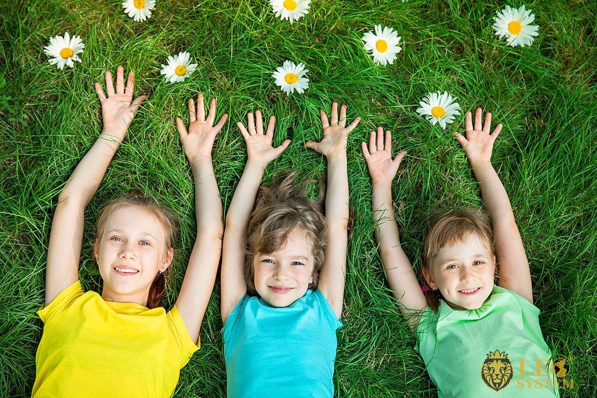 Joyful children lie on the grass with their hands up