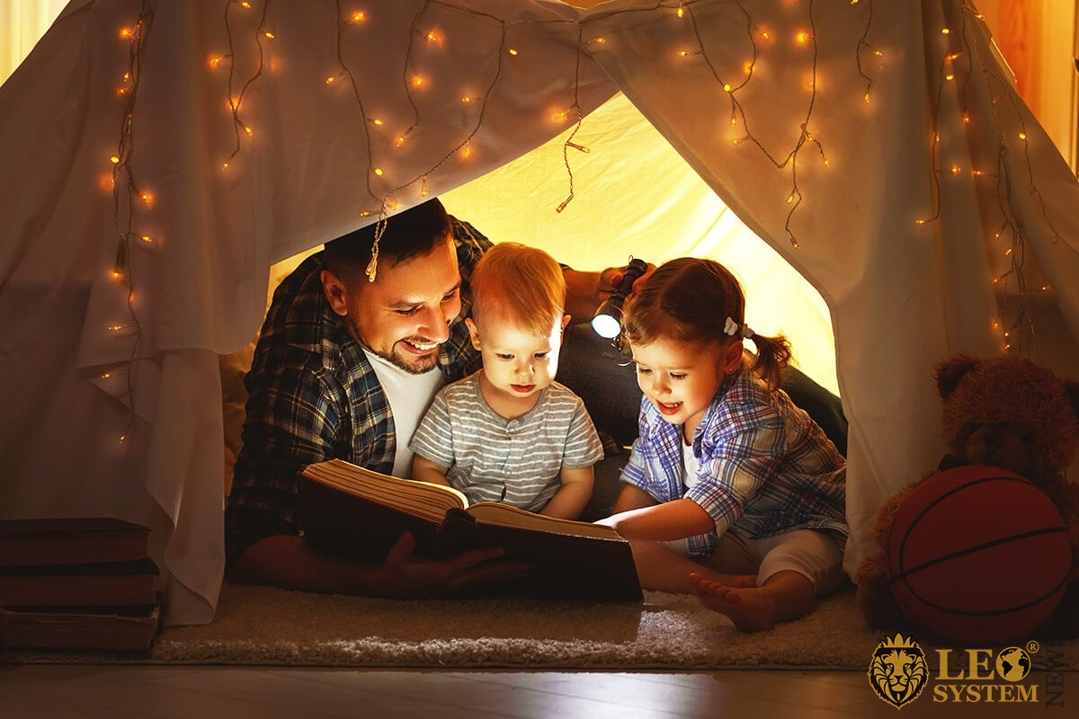 Dad with children in a small toy house reading a book