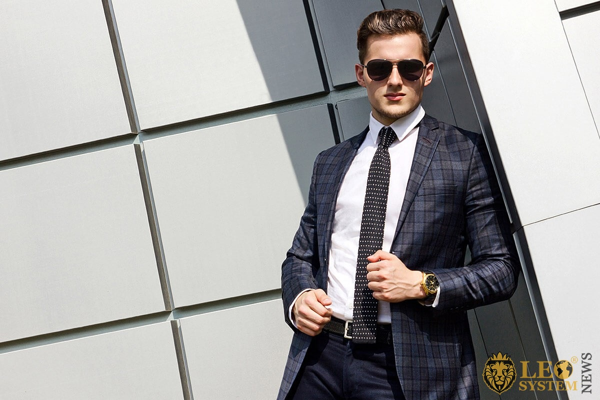 Successful man stands in a business suit and glasses