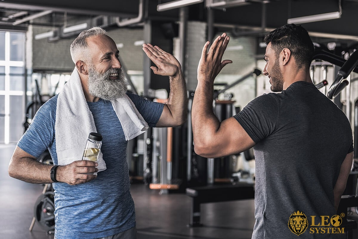 Male friendship of two men at the gym