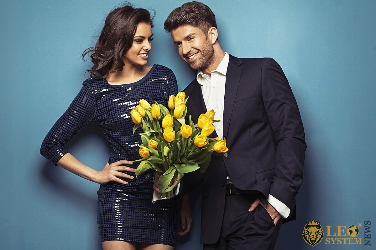 Handsome man gives a woman a bouquet of flowers