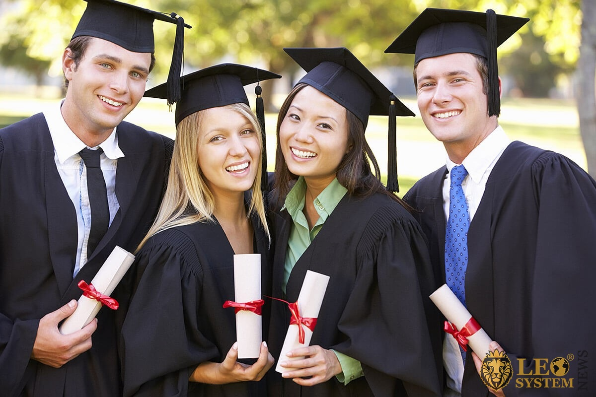 Image of graduates with diplomas in their hands