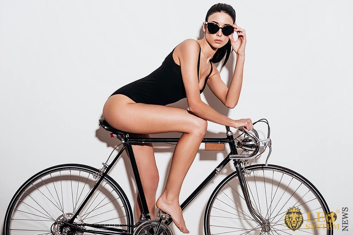 A girl with a beautiful figure sits on a bicycle