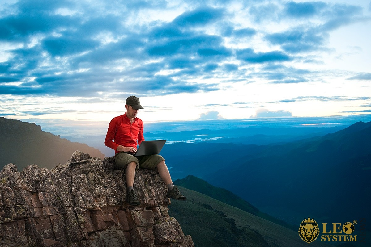 Image of a man sits on a mountain with a laptop on the Internet