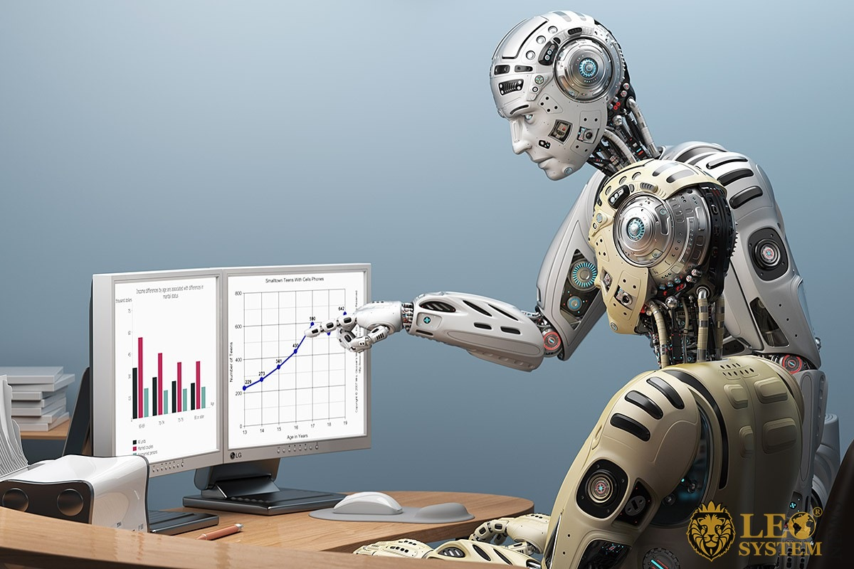 Image of two humanoid robots with a desktop computer