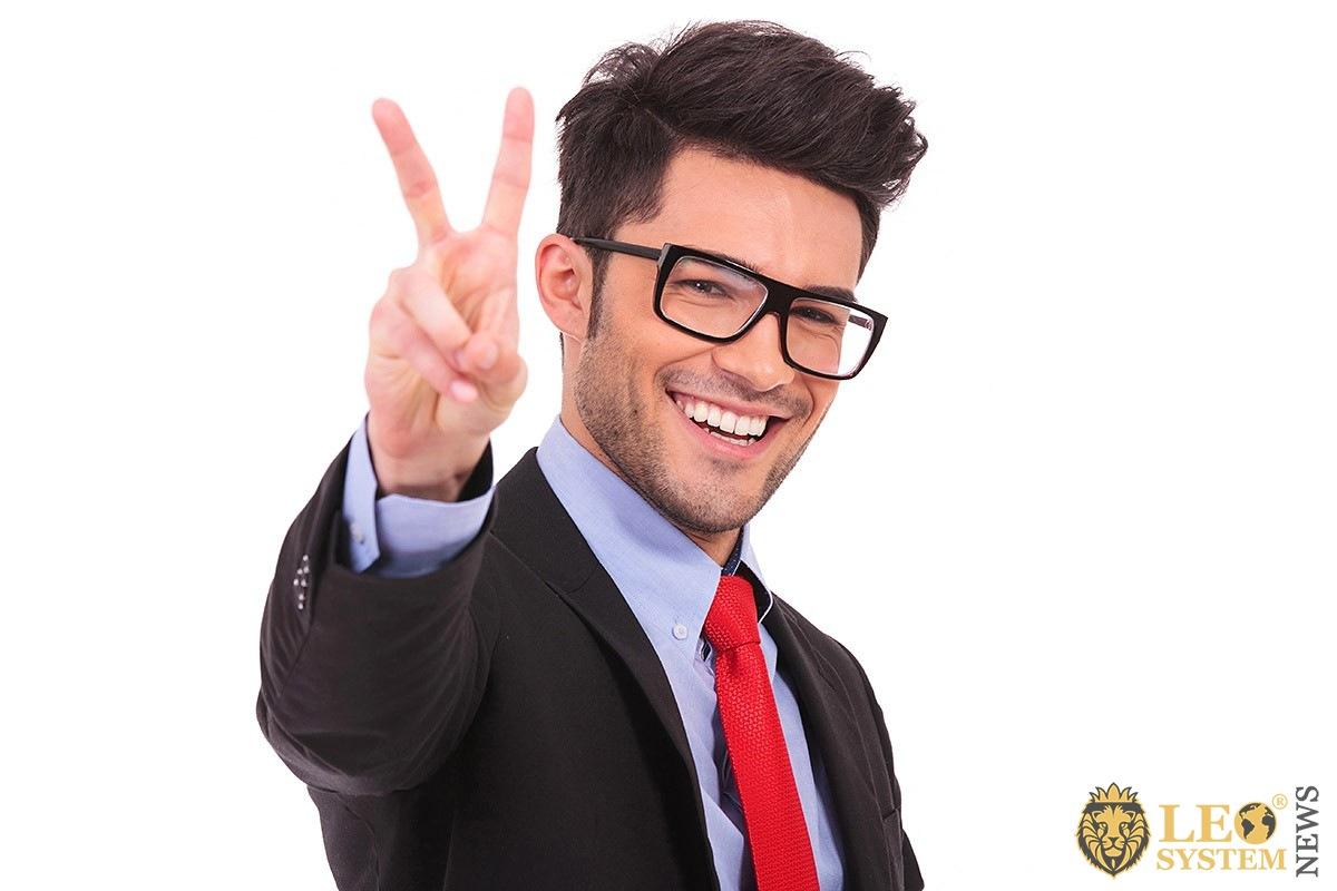 Joyful young man shows a symbol of success