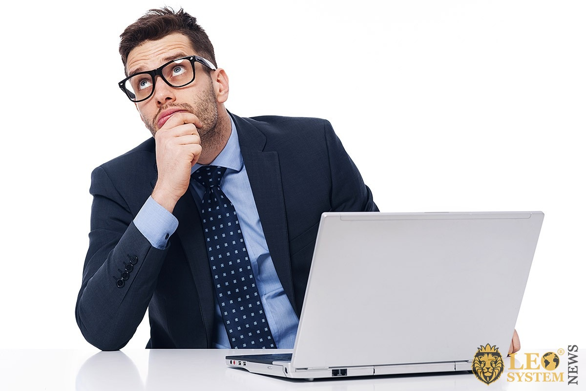 Pensive businessman with a computer