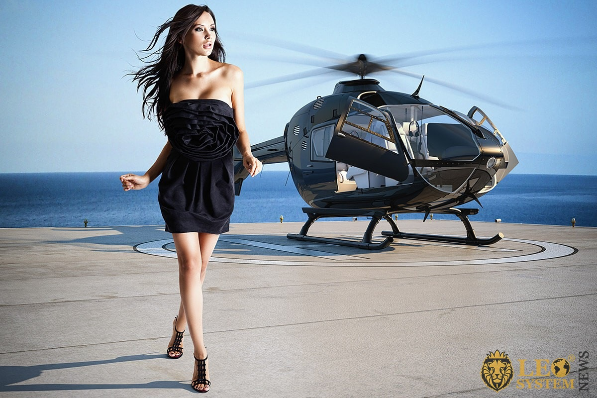 Rich girl on the background of a helicopter