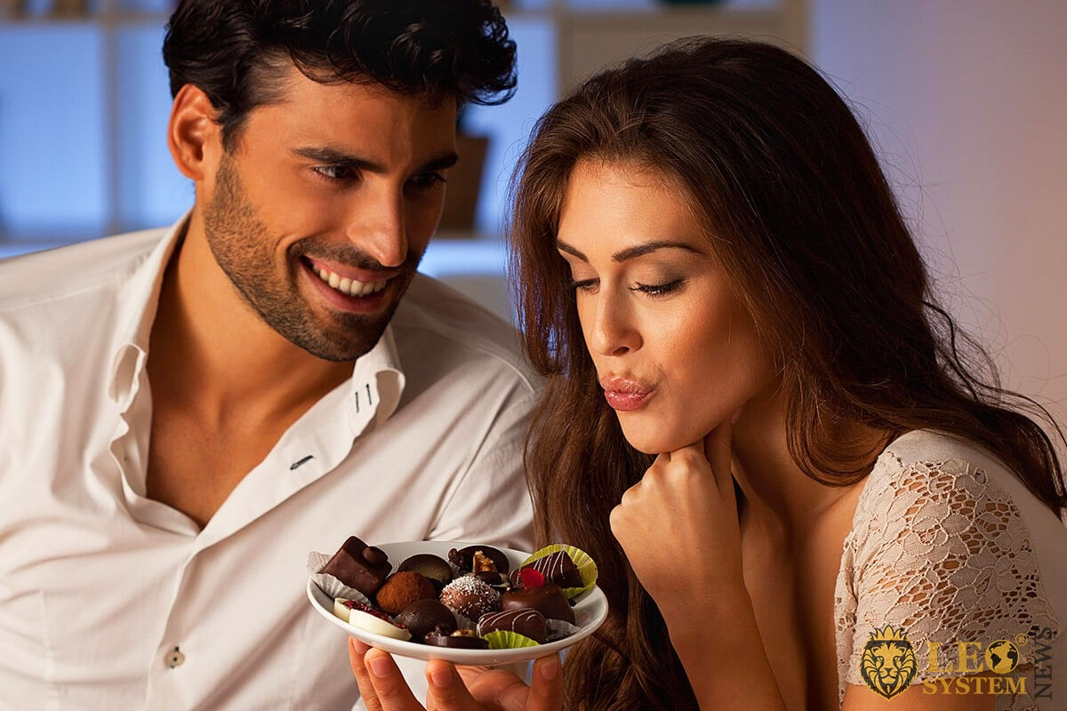 The husband offers his wife to eat chocolates