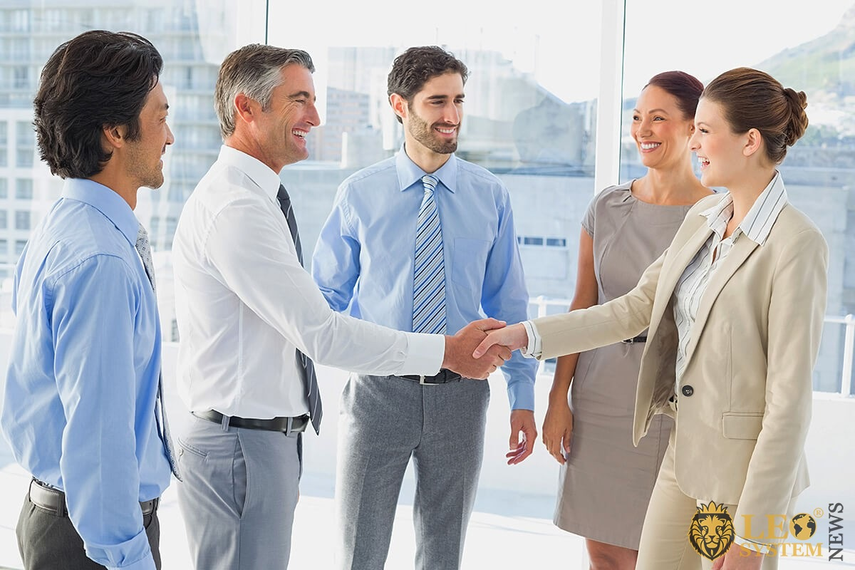 Friendly handshake of colleagues in the company