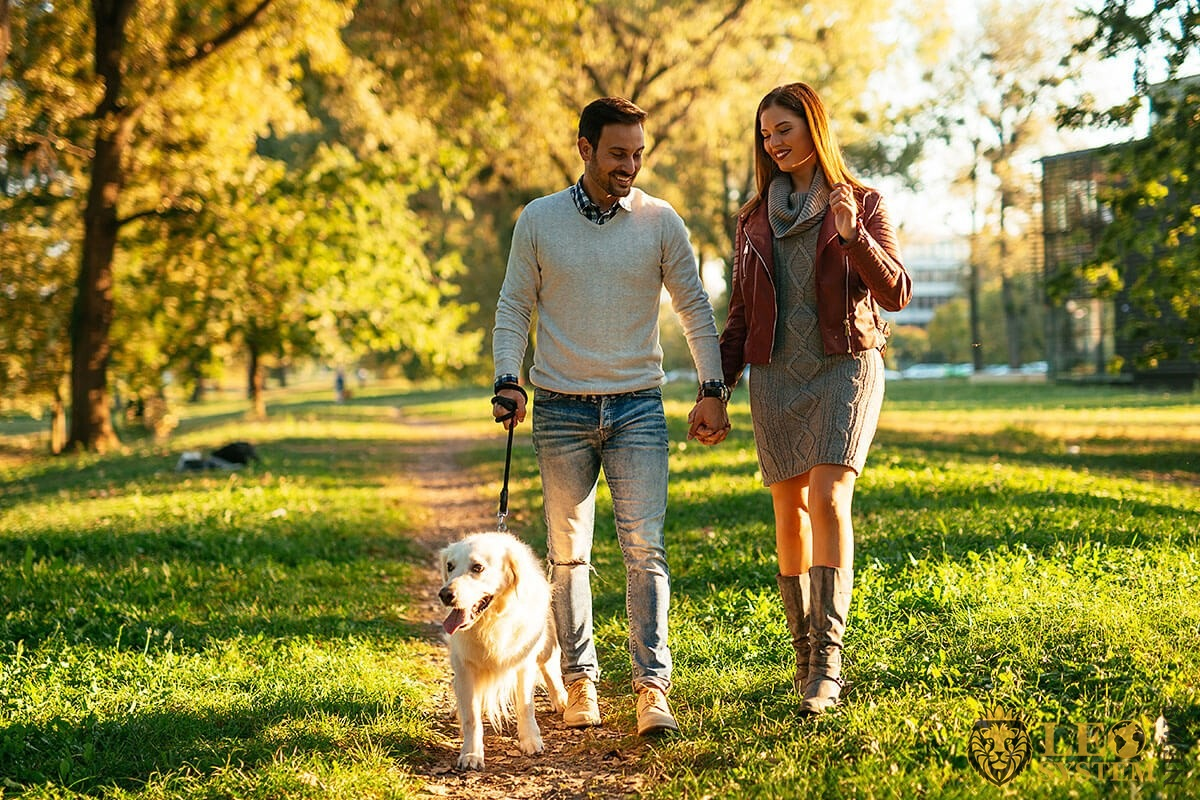 Happy couple walking in the park with a dog