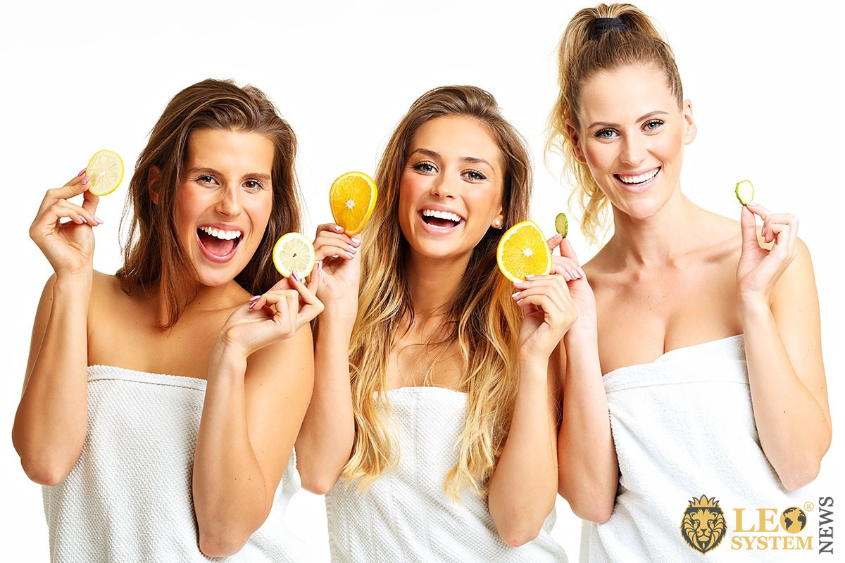 Image of well-groomed three girls with fruits in their hands