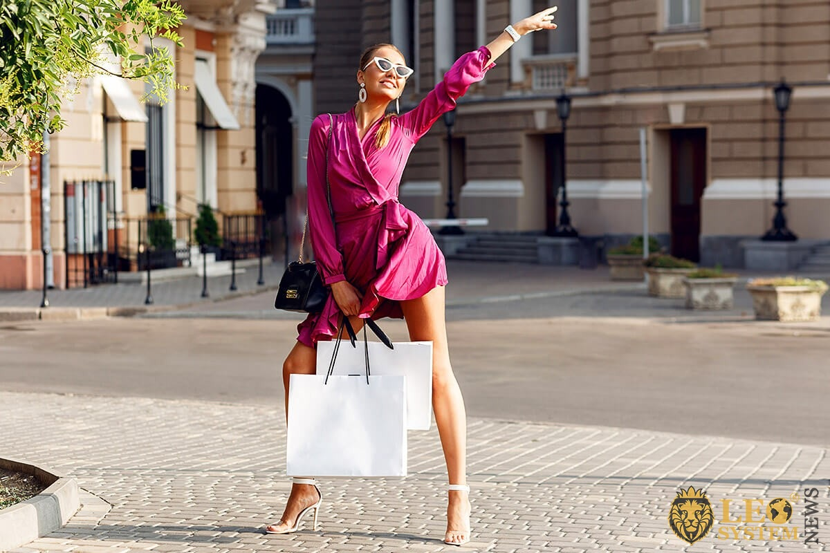 Bright woman after shopping catches a taxi
