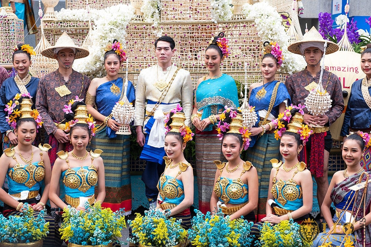 Image of men and women with flowers in their hands and traditional costumes - Flower Festival Parade, Chiang Mai, Thailand