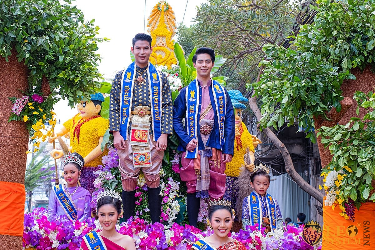 Image of men and women in traditional costumes and with flowers - Flower Festival, Thailand