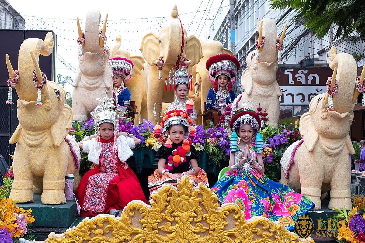 Image of women and children sitting in a flower float - Annual Flower Festival Parade, Thailand