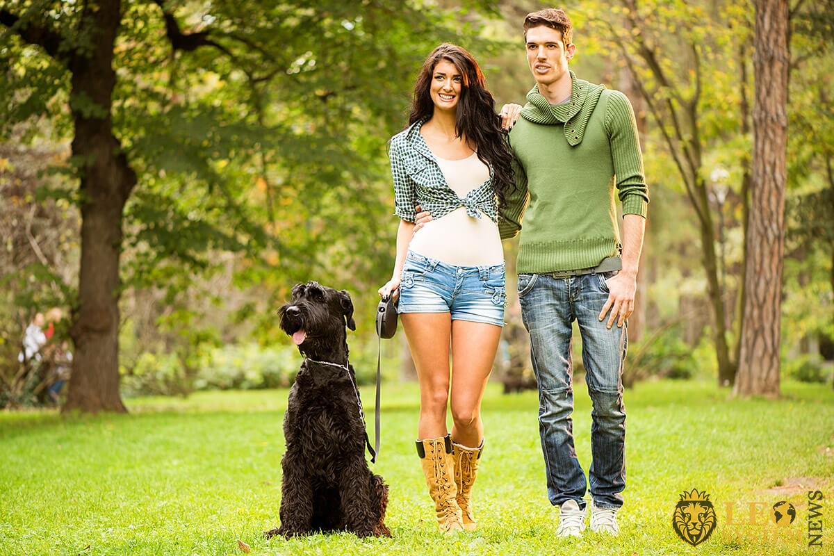 A young girl and her man are walking in the park with a dog