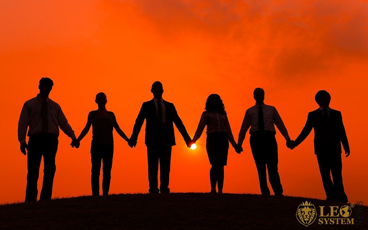 Image of a team of business people holding hands