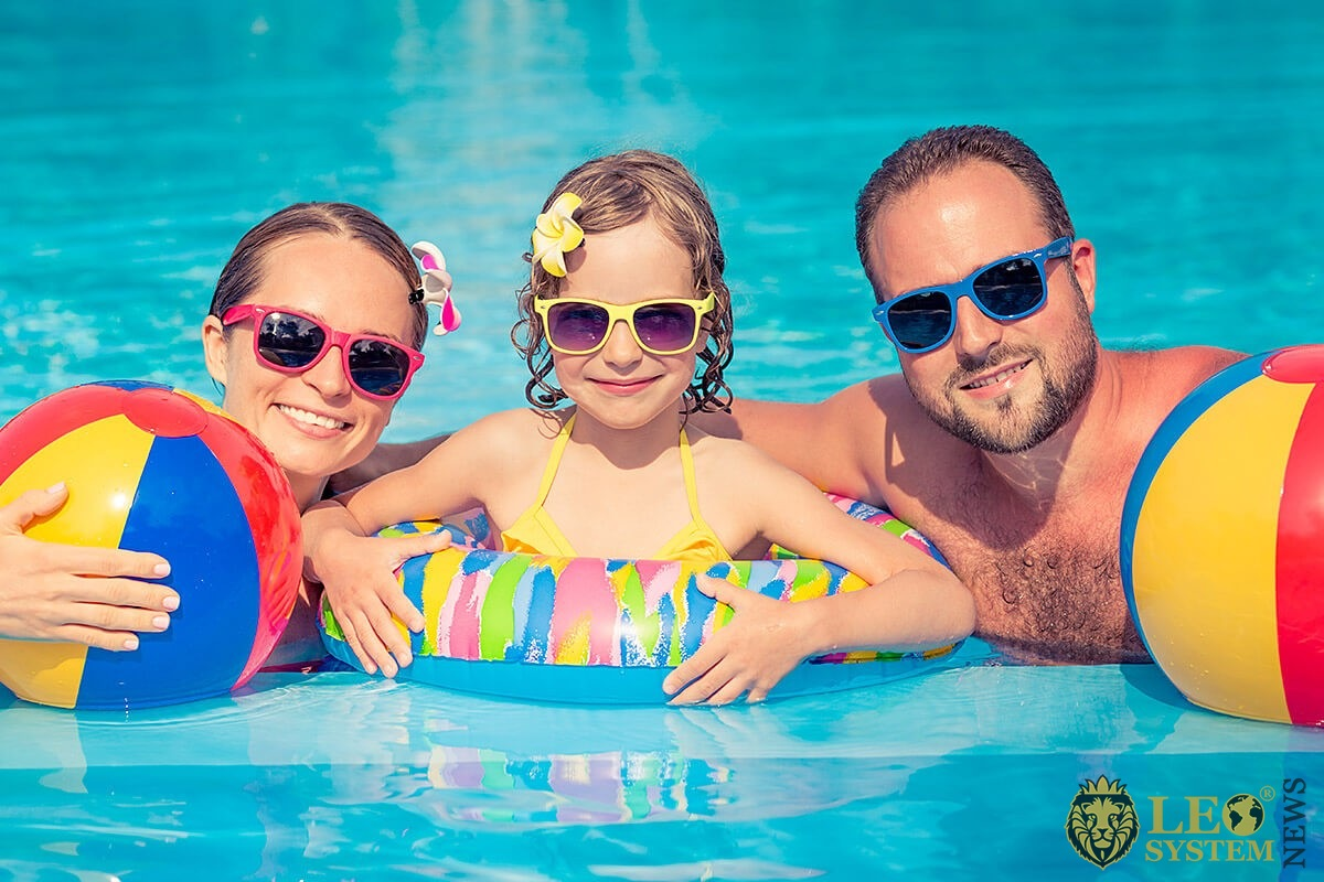 Image of a married couple and their daughter in the pool