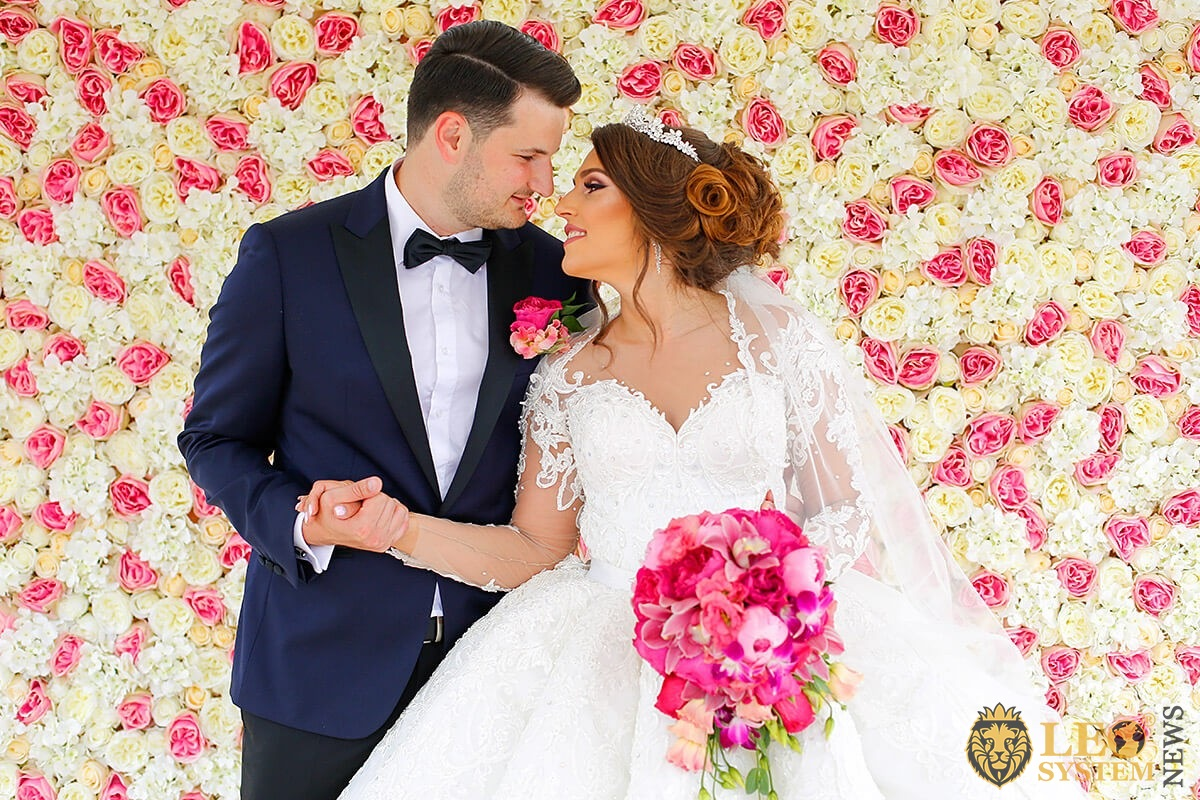 Image of a woman in a wedding dress who holds a man's hand