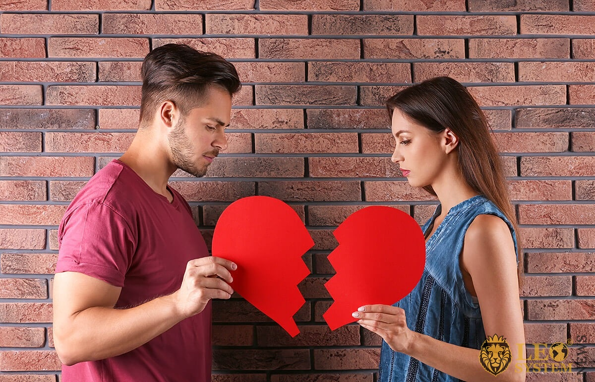 Image of man and woman with halves of paper heart in hands