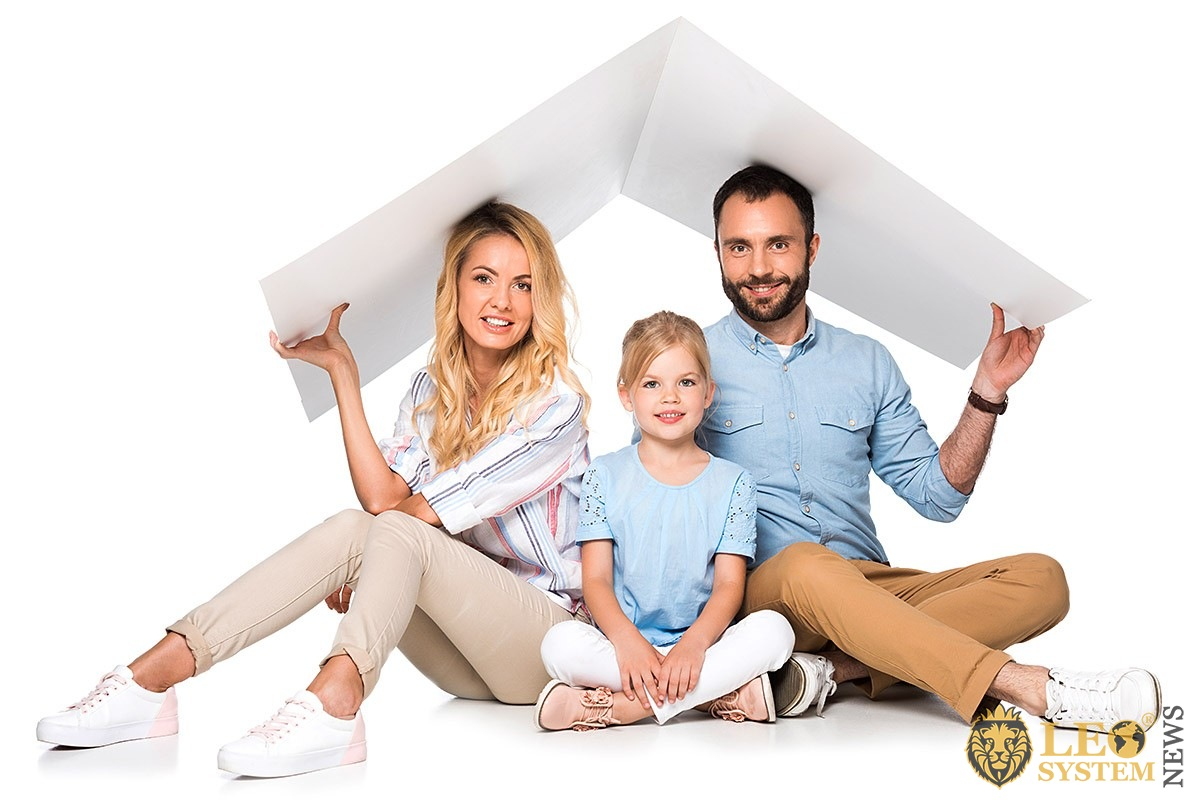 Image of a couple and a child with a paper canvas in their hands in the form of a house roof over their head