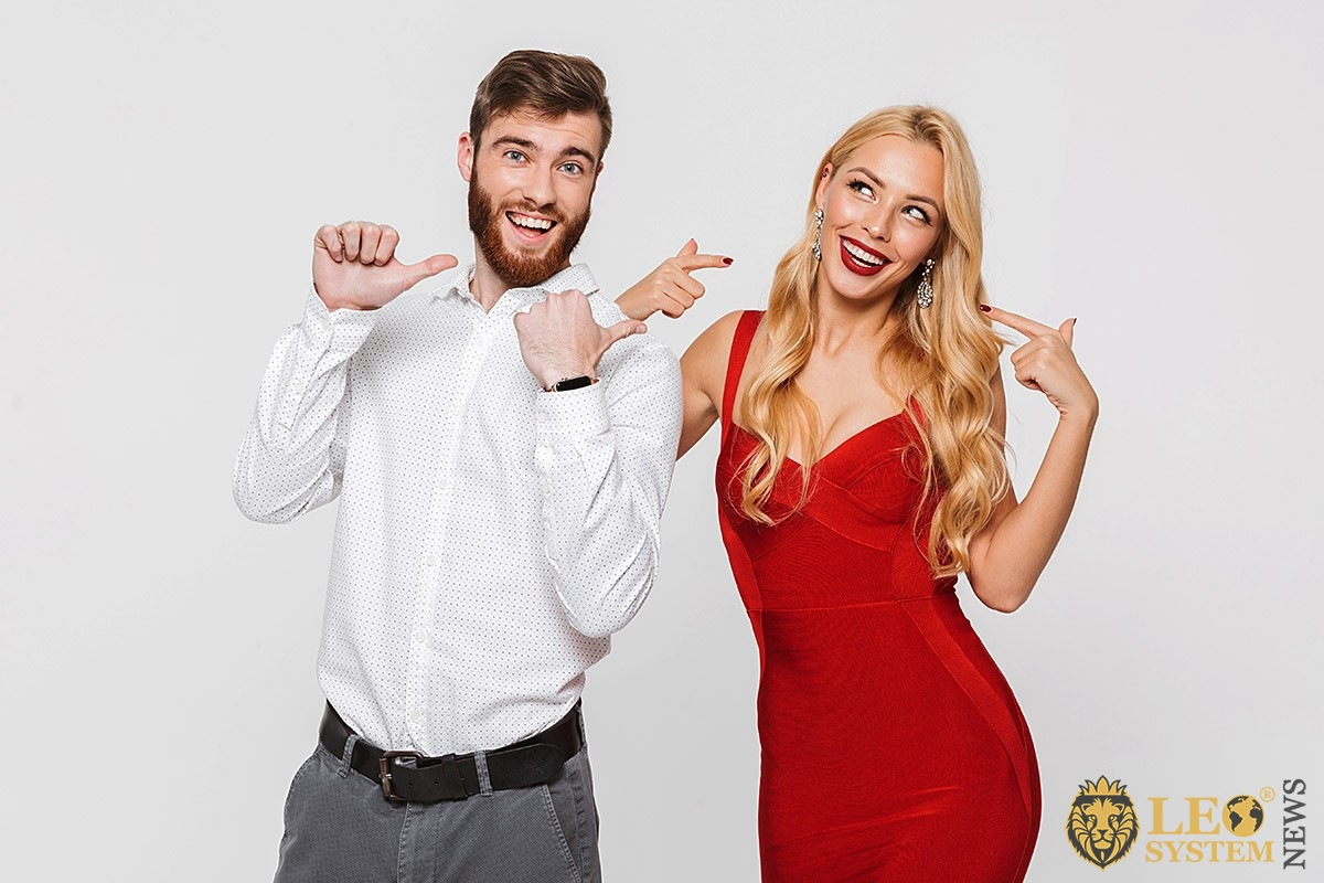 Image of a man pointing his hands at an attractive girl in a red dress