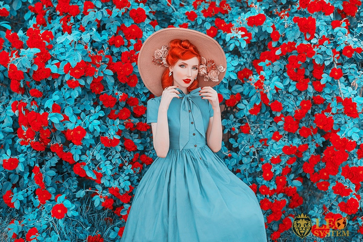 Image of a real lady in a hat and dress on a background of flowers