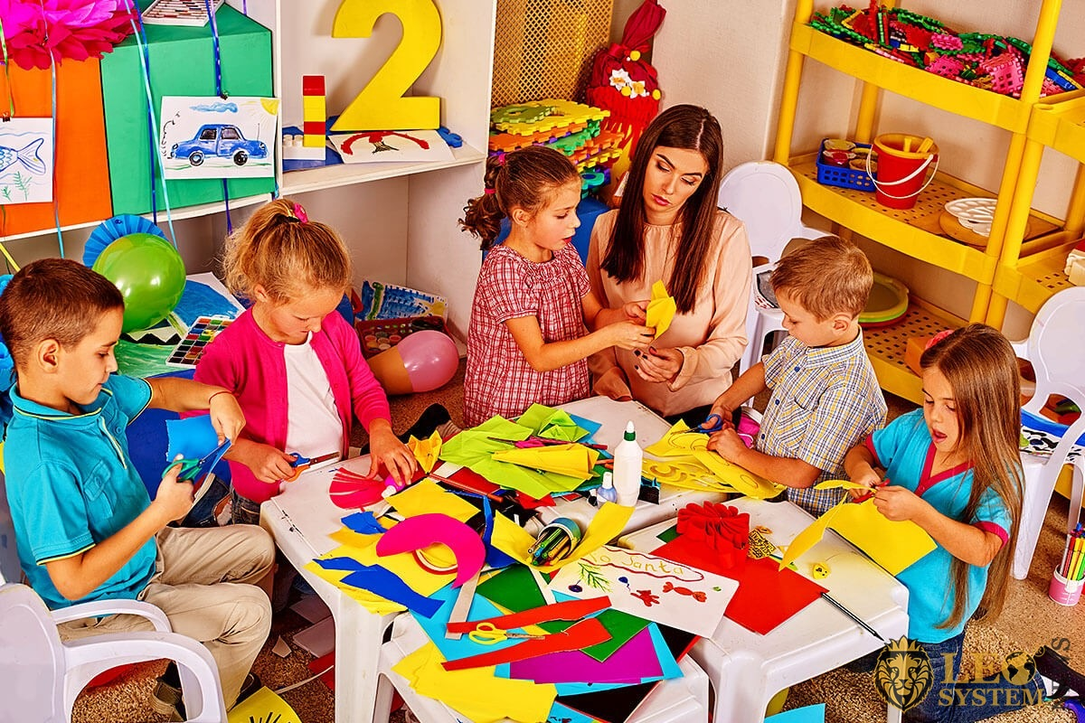 Preschool children are engaged in cutting figures out of paper with a teacher in the classroom
