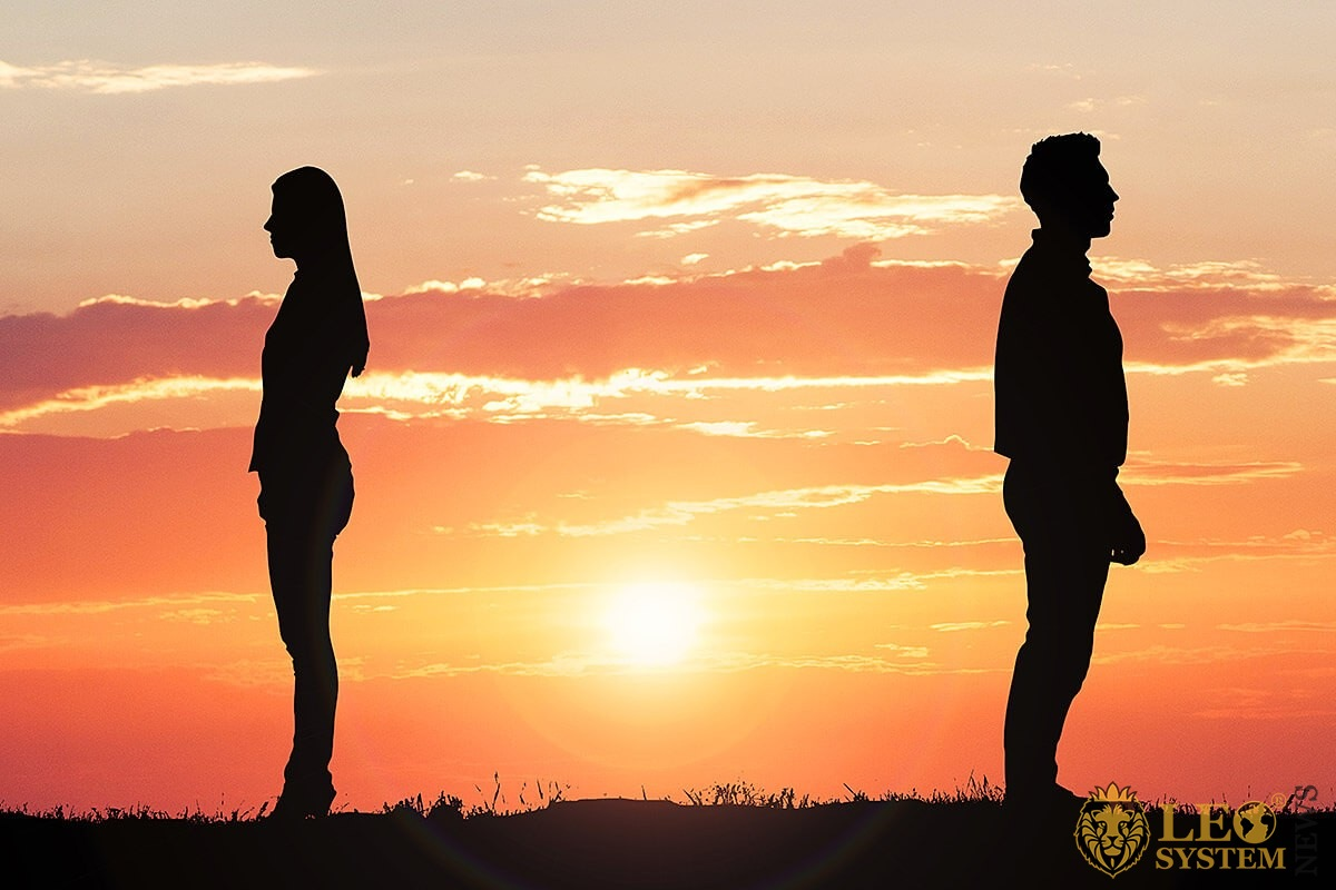 Image of man and woman standing with their backs to each other at sunset