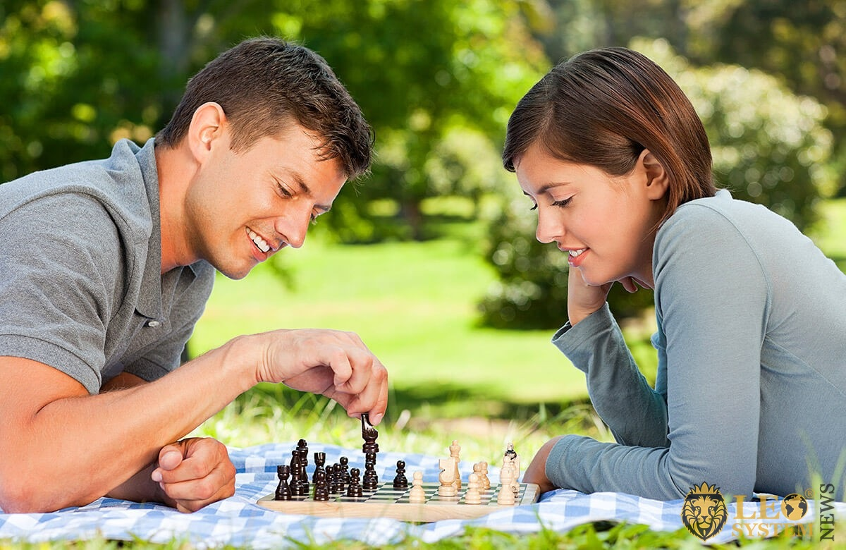 Young man plays chess lying on the grass with his girlfriend