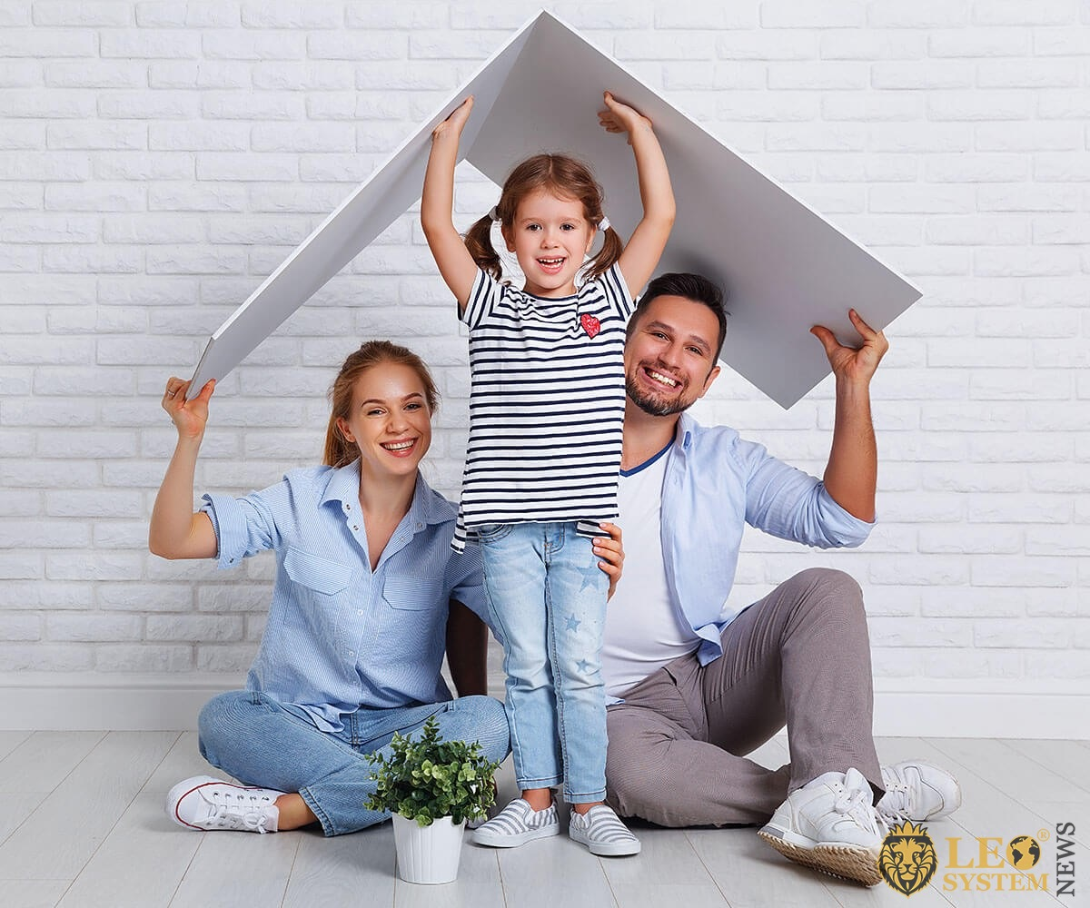 Joyful couple and a child build a house of paper together