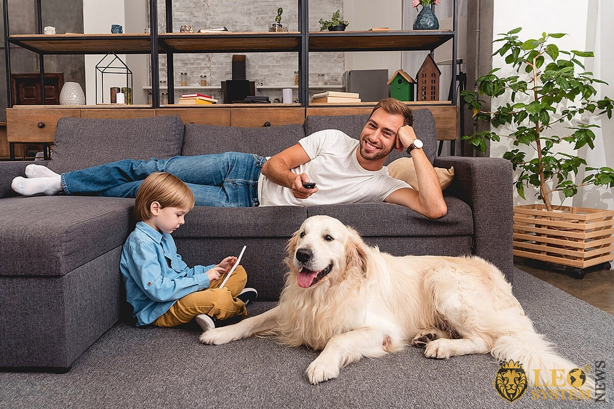 Image of a father watching TV and a child with a dog