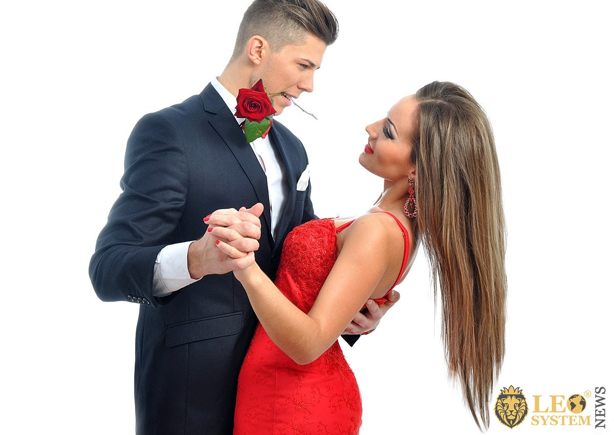 Young man with a flower in his teeth and his girlfriend in a long red dress