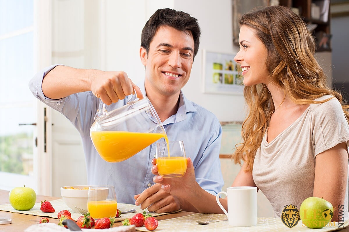 A man kindly pours juice for his woman