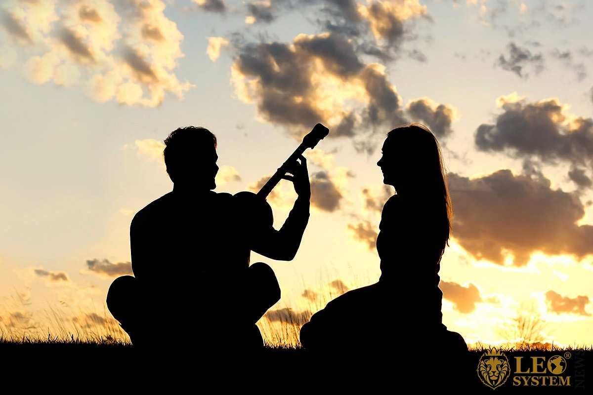 Loving man and woman at sunrise with a guitar