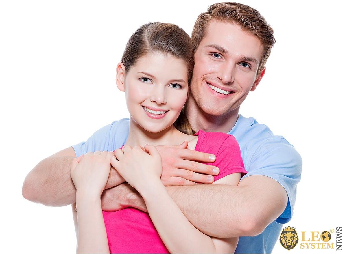Joyful man hugs his beloved woman